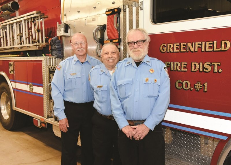 Volunteers for more than 50 years: Gordon McGrath, Robert Roxbury, and Jackie Atwell – posing for a photograph at the Greenfield Fire Station May 7, 2019 - will be recognized by the town of Greenfield for their service on Saturday. Photo by SuperSource Media.