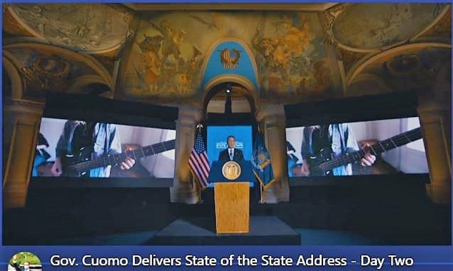 Gov. Andrew State of The State address on Tuesday, framed by twin images of a bass guitar.